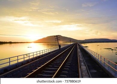 Silhouette of the floating train and mountains with the sunset sky at Pa Sak Jolasid Dam.