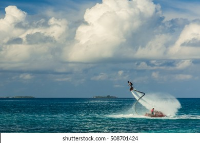Silhouette of a fly board rider at sea. Professional rider do tricks in the blue lagoon. Tropical water-sport equipment.