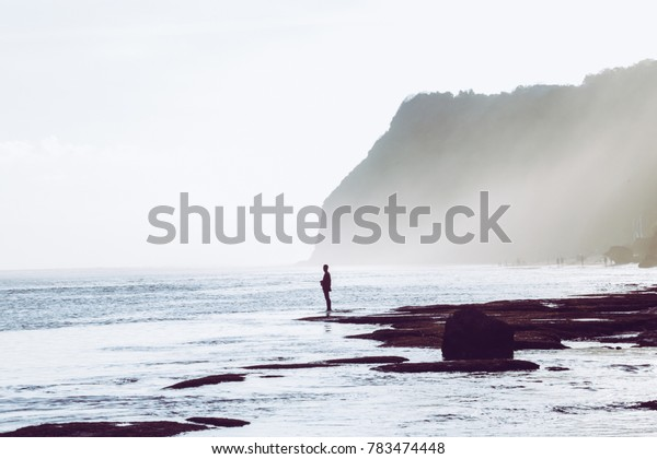 Silhouette of fly fisherman at beautiful remote beach
