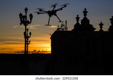 A silhouette of a flying drone with a dramatic sunset and elements of European architecture in the background.