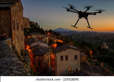 A silhouette of a flying drone with a dramatic sunset in the background in the skies of old European city