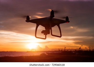 Silhouette of flying drone in sunset low lighting time.