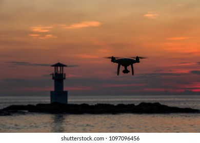 Silhouette of flying drone which taking photo over sunset sea