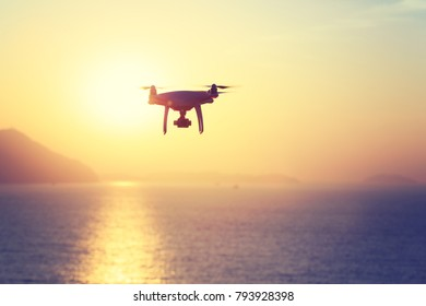 silhouette of flying drone which taking photo over sunrise sea