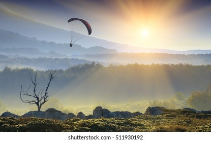 Silhouette of flying paraglide in a light of sunrise above the mountain valley.