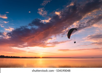 Silhouette of flying paraglide over the sea sunset.