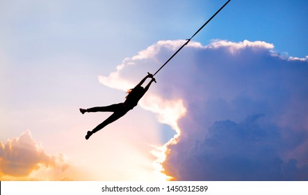 Silhouette flying in sky, silhouette girl flying on a rope bungee, human female gymnast hanging on rope against the background of clouds and sunset.