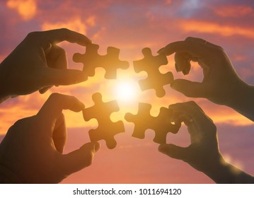 silhouette four hands trying to connect a puzzle piece with a sunset background. A puzzle in hand against sunlight. Symbol of association and communication. Business strategy. teamwork