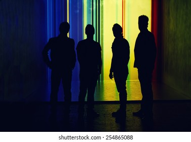 Silhouette of four people standing on highlighted wall background, team spirit concept
