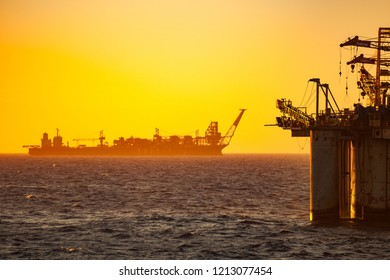 Silhouette of a FPSO oil rig (floating production storage offloading) platform ship at sunset/sunrise time, Campos Basin, Rio de Janeiro state shore, Brazil