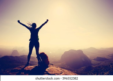 Silhouette of free cheering woman hiker open arms at mountain top cliff edge