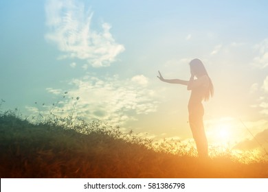 silhouette of free cheering woman hiker open arms at mountain peak beautiful sky background
