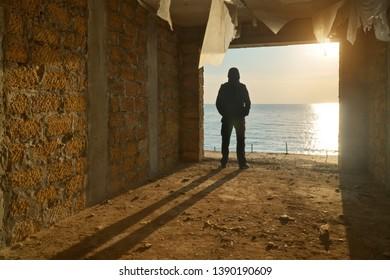 Silhouette of free man. Broken building and sea sunset. Prison escape. Conceptual scene composition.