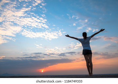 Silhouette of free woman enjoying freedom feeling happy at sunset. Serene relaxing woman in pure happiness