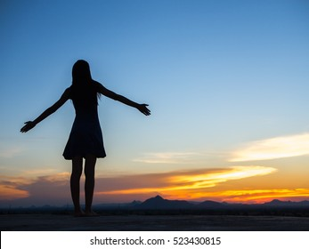 Silhouette of free woman enjoying freedom feeling happy at sunset. relaxing woman in pure happiness and elated enjoyment with arms raised outstretched up.