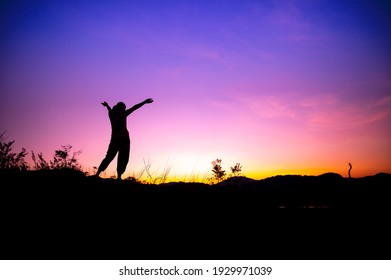 Silhouette of freedom woman standing on ground and open arms, colorful sunset sky background