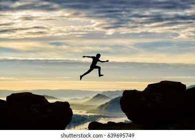 Silhouette Freedom-young man is jumping over precipice between two rocky mountains.