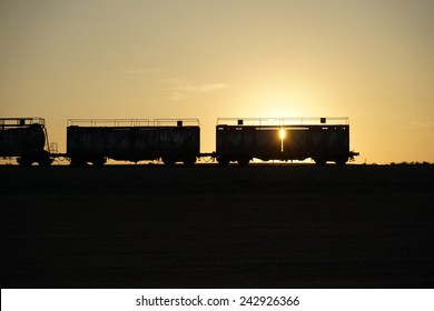 Silhouette of freight train and sunset