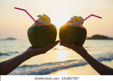 Silhouette of fresh coconut in couples hands with plumeria decorated on beach with sea wave background - tourist with fresh fruit and sea sand sun vacation background concept