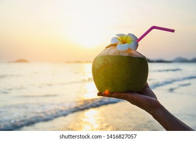 Silhouette of fresh coconut in hand with plumeria decorated on beach with sea wave background - tourist with fresh fruit and sea sand sun vacation background concept