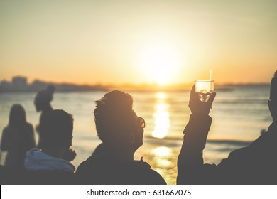 Silhouette of friends drinking cocktail on beach sunset party - Young people having fun together outdoor - Youth concept - Focus on glass - Matte filter
