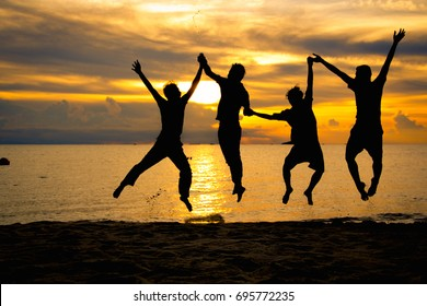 Silhouette Friends group jumping on the beach and having fun.beautiful sunset background.