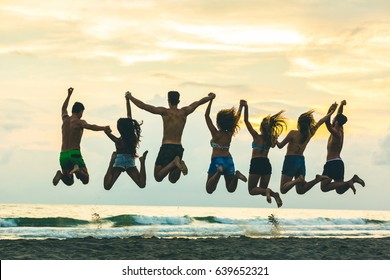 Silhouette of friends jumping on the beach. Four girls and three boys, wearing swimsuits and holding hands, having fun together at sunset. Happiness and success concepts in this colorful image.
