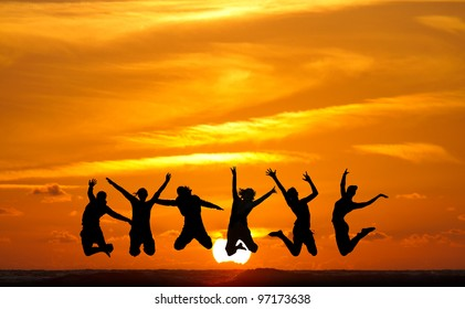 silhouette of friends jumping in sunset at beach