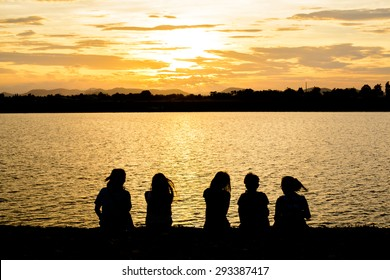 Silhouette Of Friends Sitting On Beach during sunrise time