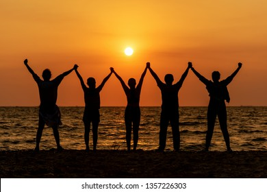 Silhouette of friends and teamwork standing on beach during sunset time for success business.  Lifestyle and Teamwork Concept