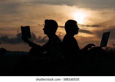 Silhouette of friends. Two man sitting on the grass work at notebook and read book. notebook versus book