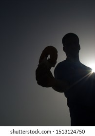 Silhouette of a fun young men buy glazed donut in beach.