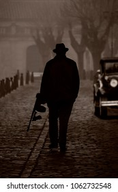 Silhouette of a gangster with machine gun, on a street with fog