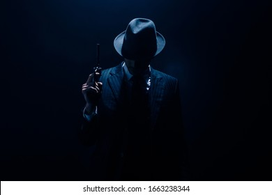 Silhouette of gangster raising gun on dark blue background