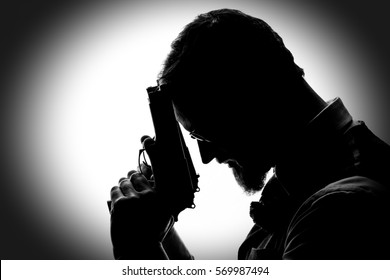 Silhouette of a gangster saying a prayer with his gun pressed to his forehead