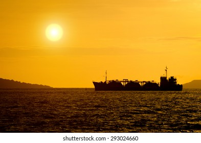Silhouette of gas tanker in the sea at sunset