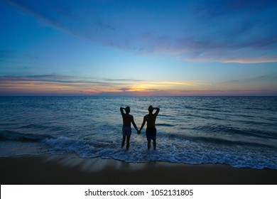 Silhouette gay couple hand in hand on the the beach and sunset time