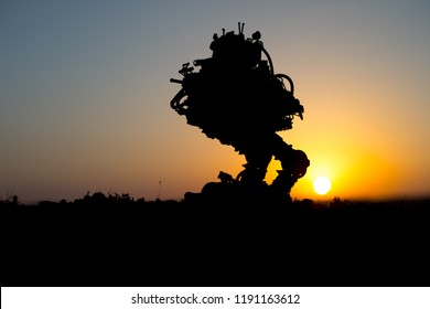 Silhouette of giant robot. Futuristic tank in action at sunset. Combat vehicle.