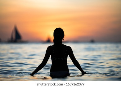 Silhouette of a girl admiring a stunning sunset on Boracay's White Beach. The White Beach de Boracay is located at Station 1, the center of the island. Philippines.