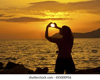 Silhouette of the girl against the backdrop of the setting sun. Sun in hands. Heart
