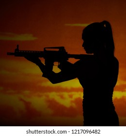 Silhouette of girl aiming with carbine in sunset
