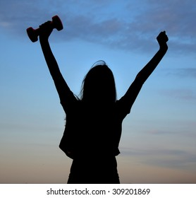 silhouette of girl athletes (with dumbbells in hand) athletic girl at sunrise