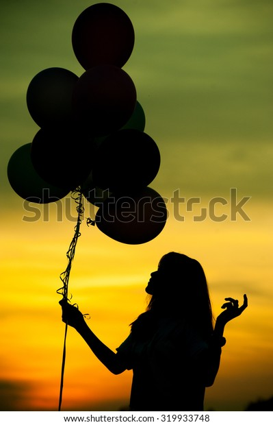 Silhouette of girl with balloon.