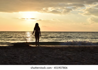 silhouette of a girl with beach sunset