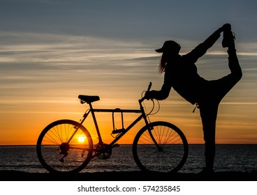 Silhouette of girl with bicycle at sunset time. Young woman is doing yoga near the ocean with bicycle