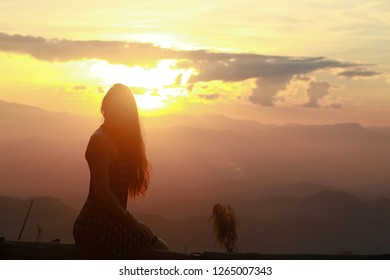 silhouette of a girl and a camera on a background of sunset in the mountains