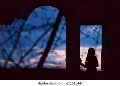 Silhouette of a girl with a candle in windowed ancient openings. Dark photo, view of the sunset in the background. Art photo among the ancient ruins. Mysterious mysterious situation.