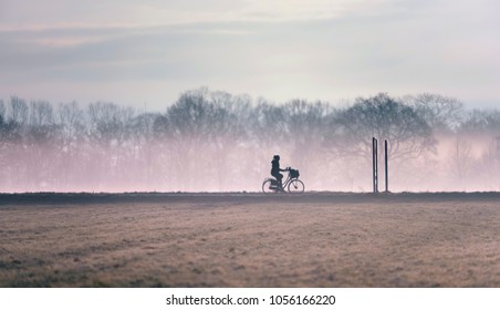 Silhouette of girl cycling on misty country road.