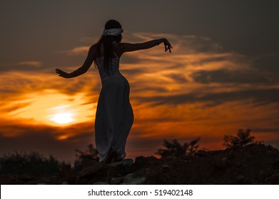 Silhouette of a girl dancing Oriental dance at sunset.
