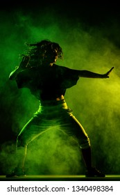 silhouette of a girl dancing with smoke in the background